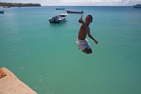 Niño jugando y saltando en el puerto de la Isla